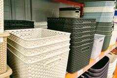 五颜六色的塑料盒堆积了一在其他 在货架的多彩多姿的塑料篮子 免版税库存照片