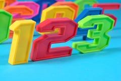 五颜六色的塑料第123在蓝色背景 免版税库存照片