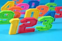 五颜六色的塑料第123在蓝色背景 库存图片