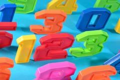 五颜六色的塑料第123在蓝色背景 免版税库存图片