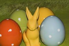 五颜六色的复活节彩蛋和一只复活节兔子在绿色背景前面 库存图片