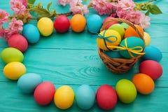 五颜六色的复活节彩蛋和篮子在蓝色木桌背景 顶视图和拷贝空间 食物鸡蛋,花 乐趣假日 免版税库存图片