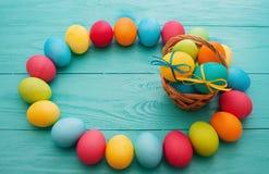 五颜六色的复活节彩蛋和篮子在蓝色木桌背景 顶视图和拷贝空间 食物鸡蛋 乐趣假日 免版税库存图片