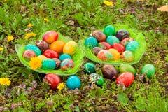 五颜六色的复活节彩蛋在有花的一个草甸安排了 图库摄影