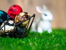 五颜六色的复活节彩蛋在篮子 安置在绿草 有一只逗人喜爱的兔子在后面 后面是一个棕色木框架 免版税库存图片