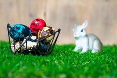 五颜六色的复活节彩蛋在篮子 安置在绿草 有一只逗人喜爱的兔子在后面 后面是一个棕色木框架 图库摄影