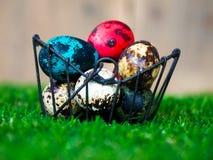 五颜六色的复活节彩蛋在篮子 安置在绿草 有一只逗人喜爱的兔子在后面 后面是一个棕色木框架 免版税库存照片