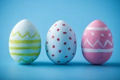 五颜六色的复活节彩蛋手画在蓝色背景 假日春天卡片 免版税库存图片