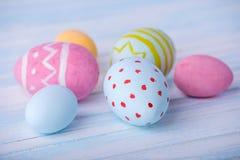 五颜六色的复活节彩蛋手画在蓝色背景 假日春天卡片 库存照片