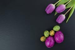 五颜六色的复活节和鹌鹑蛋和郁金香花在石桌上 与拷贝空间的顶视图 免版税库存照片