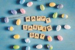 五颜六色的复活节彩蛋和木头发短信给在蓝色浆糊的愉快的复活节天 免版税库存照片