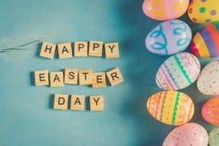 五颜六色的复活节彩蛋和木头发短信给在蓝色浆糊的愉快的复活节天 库存图片
