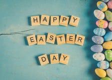 五颜六色的复活节彩蛋和木头发短信给在蓝色浆糊的愉快的复活节天 图库摄影
