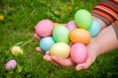 五颜六色的复活节彩蛋在绿色草坪的手上 库存图片