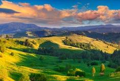 五颜六色的夏天日出在喀尔巴阡山脉的村庄 免版税库存照片