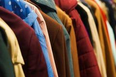 五颜六色的外套在慈善商店 免版税库存图片