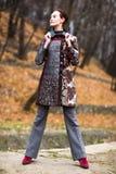五颜六色的外套的美丽的夫人在秋天摆在 免版税库存图片
