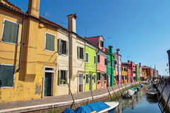 五颜六色的大厦、人和小船看法在一条运河前面在Burano 免版税库存照片