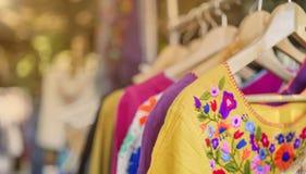 五颜六色的妇女穿戴垂悬在路轨在室外市场上 免版税库存照片