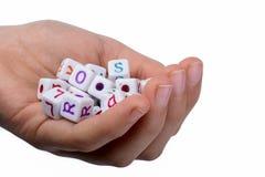 五颜六色的字母表在手中在立方体上写字 免版税库存图片