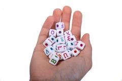 五颜六色的字母表在手中在立方体上写字 库存照片