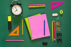 五颜六色的学校用品、桃红色书和闹钟在绿色 顶视图,平的位置,拷贝空间 库存图片