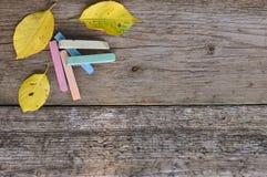 五颜六色的学校蜡笔和黄色叶子在木背景 土气 9月1日 免版税库存图片