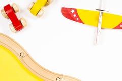 五颜六色的孩子戏弄在白色背景的平面和木汽车 免版税库存图片