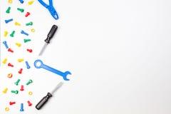 五颜六色的孩子玩具边界 塑料玩具工具、螺栓和坚果在白色背景 顶视图 库存照片
