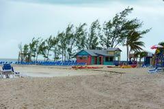 五颜六色的客舱、塔、棕榈树和沙子 库存图片