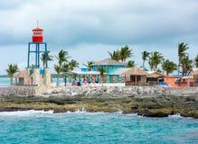 五颜六色的客舱、塔、棕榈树和沙子 免版税图库摄影