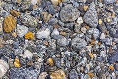 五颜六色的小卵石在水中 免版税库存图片