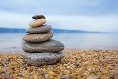 五颜六色的小卵石金字塔  晃动禅宗在海的背景中 和谐和平衡的概念 库存图片