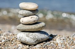 五颜六色的小卵石金字塔  晃动禅宗在海的背景中 和谐和平衡的概念 库存照片