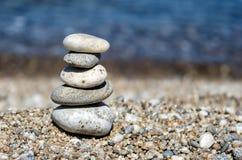 五颜六色的小卵石金字塔  晃动禅宗在海的背景中 和谐和平衡的概念 免版税库存图片