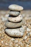 五颜六色的小卵石金字塔  晃动禅宗在海的背景中 和谐和平衡的概念 免版税图库摄影