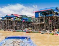 五颜六色的小船和高跷房子在部落Phluk浮动村庄, Tonle Sap湖,柬埔寨 免版税库存照片