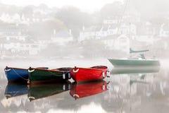 五颜六色的小船在有薄雾的德文郡港口 免版税库存照片