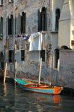 五颜六色的小船被栓对与垂悬在背景中的洗涤物的老大厦 库存图片