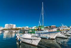 五颜六色的小船,晴朗的早晨在St安东尼de Portmany,伊维萨岛镇,巴利阿里群岛,西班牙港口  免版税库存图片