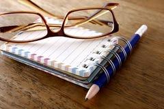 五颜六色的小螺纹笔记本、镜片和一支铅笔在一张木桌上 库存照片
