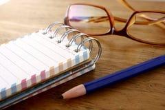 五颜六色的小螺纹笔记本、镜片和一支铅笔在一张木桌上 免版税图库摄影