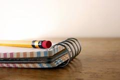 五颜六色的小螺纹笔记本和一支铅笔在一张木桌上 库存图片