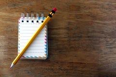 五颜六色的小螺纹笔记本和一支铅笔在一张木桌上 免版税图库摄影
