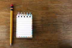 五颜六色的小螺纹笔记本和一支铅笔在一张木桌上 免版税库存照片