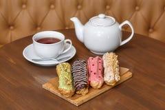 五颜六色的小饼结块与奶油和茶壶在木板 图库摄影