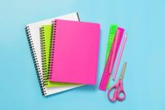 五颜六色的少女学校用品、笔记本和笔在有魄力的蓝色 顶视图,平的位置 复制空间 免版税库存图片
