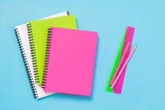 五颜六色的少女学校用品、笔记本和笔在有魄力的蓝色 顶视图,平的位置 复制空间 免版税图库摄影