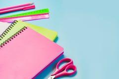 五颜六色的少女学校用品、笔记本和笔在有魄力的蓝色 顶视图,平的位置 复制空间 库存图片