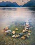 五颜六色的岩石在有背景山的湖 图库摄影